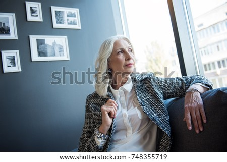 Elegant serious businesswoman is sitting on couch