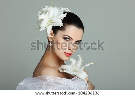 Elegant sexual brunette in a wedding-dress with lilies in hairs - stock photo