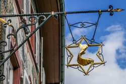 Elegant signboard made of cast iron and glistening gold, depicting a fish in a star shape. Attached to a facade in the old town of Rheinfelden, canton of Aargau, Switzerland.