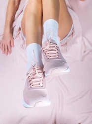 Elegant slim legs of girl in pink sport shoes and in light transparent, cipher skirt lying on knitted plaid. Pastel pink color concept. Above, top view, flat lay. Lifestyle fasion