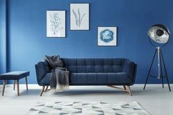 Elegant sofa, vintage lamp and footstool in stylish room