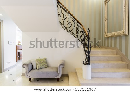 Elegant staircase with decorative railing, big framed mirror and patterned couch #537151369