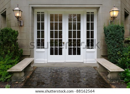 Elegant stone walkway bordered by stone benches leading to a double glass paned front door with two large front lanterns - stock photo