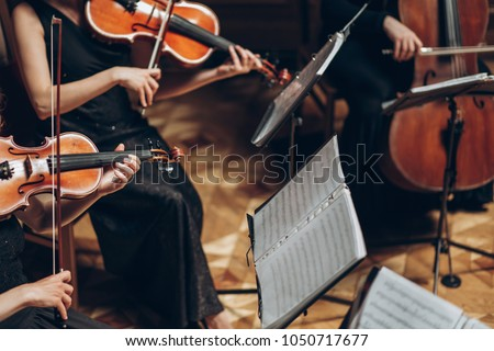 Elegant string quartet playing in luxury room at wedding reception in restaurant. group of people in black performing on violin and cello at theatre orchestra, music concept