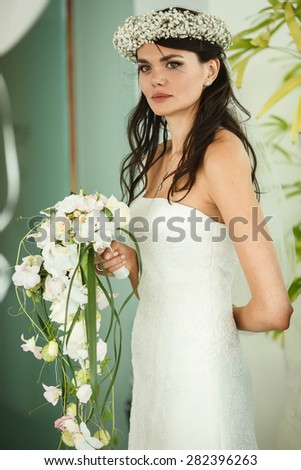 elegant stylish bride with bouquet of orchids on the background restaurant