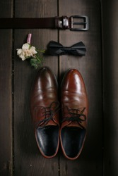 Elegant stylish brown leather male shoes with small wedding flower boutonniere, bow tie isolated on wooden floor. Preparation for wedding.