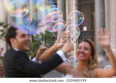 elegant stylish groom with his happy gorgeous blonde bride have fun with soap bubble #1024685599