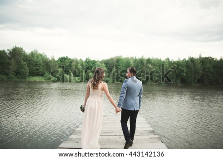 elegant stylish groom with his happy gorgeous brunette bride on the background of a lake #443142136