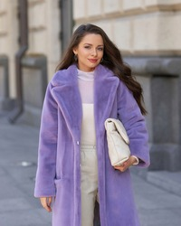 Elegant stylish woman with long brunette wavy hair wearing white trousers, pullover and shoes and purple fur coat walking city street on a sunny day