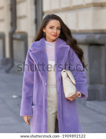 Elegant stylish woman with long brunette wavy hair wearing white trousers, pullover and shoes and purple fur coat walking city street on a sunny day Photo stock ©