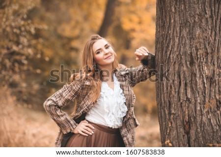 Elegant stylish woman 24-26 year old lean on tree wearing trendy jacket and white vintage top posing outdoors over nature background closeup. Looking at camera. Autumn season. 20s.  Photo stock ©