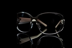 Elegant sunglasses on black background