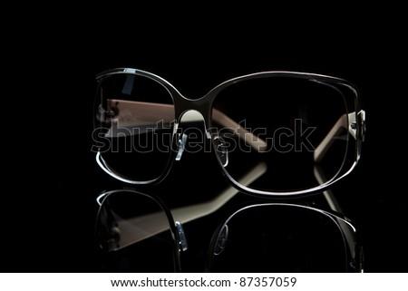 Elegant sunglasses on black background