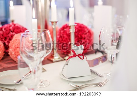 Elegant table set  for wedding or event party in soft red and pink, with paper bride and groom