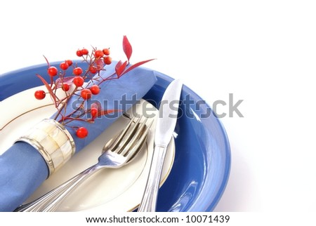 Elegant table setting in blue and white, with fresh sprigs of leaves and berries