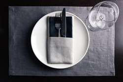 Elegant table setting white plates on black wooden table, tableware served empty table in a restaurant, Empty glasses, luxury tableware concept