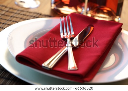 Elegant table setting with fork, knife and red napkin - stock photo