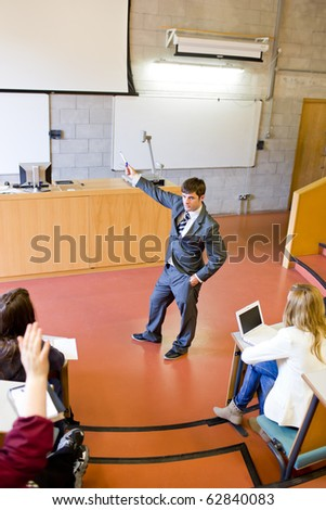 Elegant teacher giving a lesson to university students in an auditorium