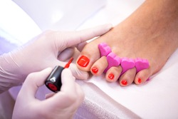 Elegant toe nails polishing, red toe nail polisher, pedicure spa