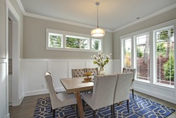 Elegant transitional dining room with board and batten walls, wood table surrounded by grey upholstered chairs.