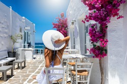 Elegant traveller woman enjoys the classic setting of white houses and colorful flowers on the cyclades islands of Greece during summer time