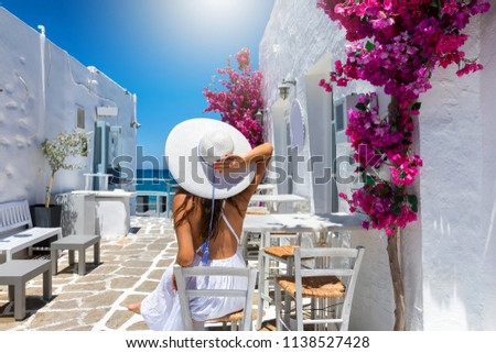 Elegant traveller woman enjoys the classic setting of white houses and colorful flowers on the cyclades islands of Greece during summer time Foto d'archivio ©