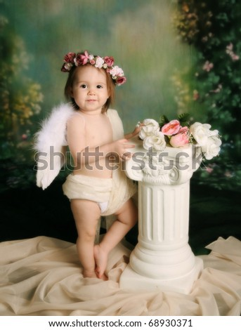 Elegant vintage style portrait of a baby girl dressed with angel wings and a flower halo headband