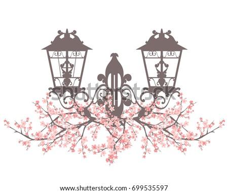 elegant vintage style street light among blooming sakura branches - spring season urban decor design