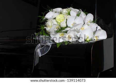 Elegant wedding bouquet made with white flowers on black piano