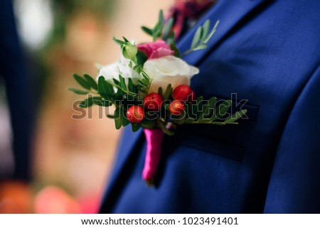 96ad4f420237 elegant wedding boutonniere of white and pink roses on the groom's blue  jacket closeup #1023491401