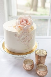 Elegant wedding cake with edible rose topper and lace piping design.