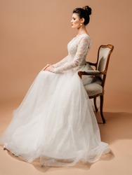 Elegant wedding dress. Beautiful brunette bride sitting in a vintage chair. Wedding traditions. Gravely studio portrait on brown background. Marriage duty concept.