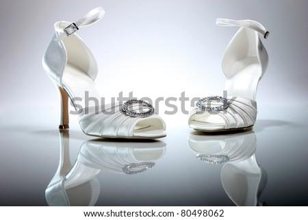 stock photo Elegant wedding shoes over gradient gray background