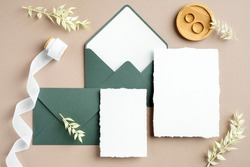 Elegant wedding stationery set. Wedding invitation cards templates, green envelopes, silk ribbon, golden rings on pastel beige background. Flat lay, top view, copy space.