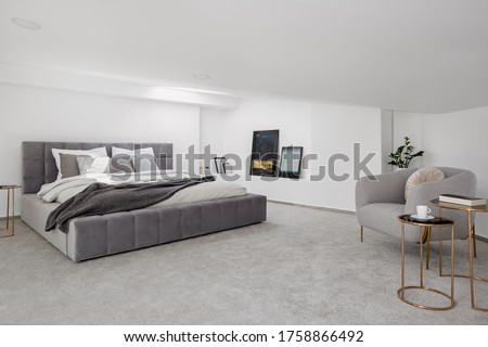 Elegant white, attic bedroom with big, gray quilted bed and armchair with two golden coffee tables