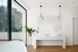 Elegant white bathroom interior with big window, wooden floor and two washbasins
