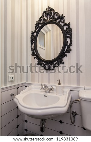 Elegant white sink and oval mirror in toilet