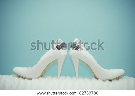 Elegant white wedding shoes over gradient blue background