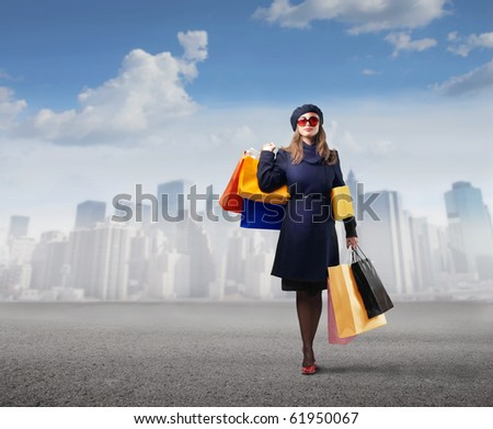 Elegant woman carrying some shopping bags with cityscape on the background
