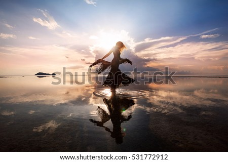 Elegant woman dancing on water. Sunset and silhouette. #531772912