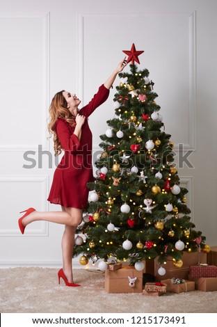 Elegant woman decorating the christmas tree  #1215173491