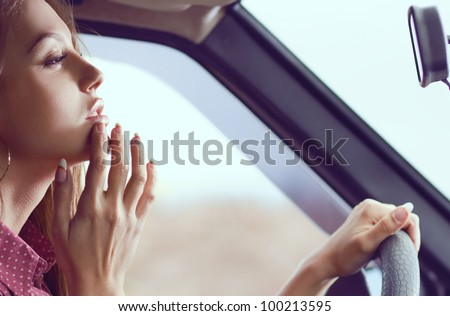 Elegant woman doing makeup in the while driving