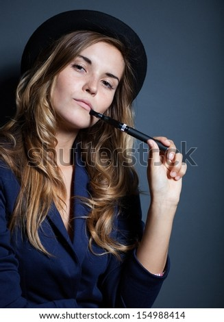 Elegant woman holding and smoking e-cigarette