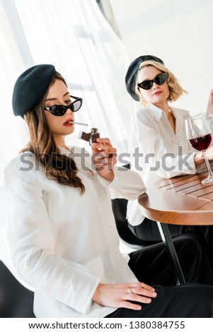 fba4048ee0269 elegant woman in black beret and sunglasses lighting up cigarette near  friend  1380384755