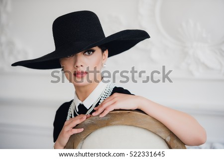 Elegant woman in black dress with a hat sitting on chair #522331645