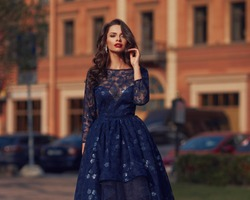 Elegant woman in blue ball gown dress standing and posing on a sunny evening at city street. Fashion model full length portrait