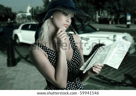 elegant woman in blue polka dot dress and hat looking at a tourist map