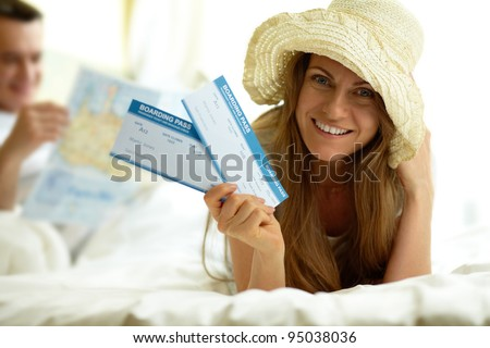 Elegant woman in hat holding flight tickets and looking at camera