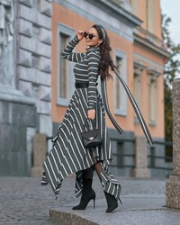 Elegant woman in long warm dress with grey and white stripes walking at city street. Female model with long wavy brunette jair in sunglasses with black leather handbag