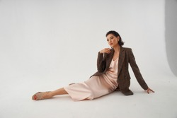 Elegant woman in peach color silk slip dress and brown squared wool blazer sitting and posing in studio at white background. Pretty stylish brunete girl with makeup and wet hair full length portrait